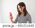Smiling woman surfing smartphone at home 69151440