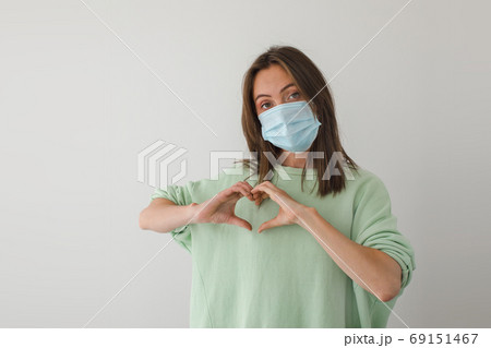 Woman in medical mask hands heart 69151467