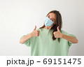 Caucasian young woman with disposable face mask 69151475