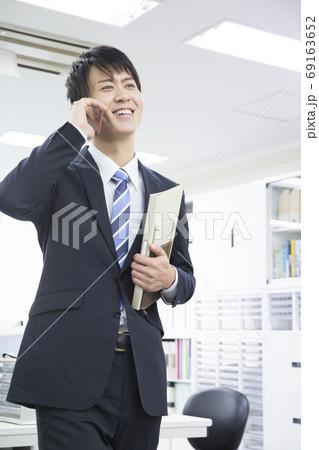 スマートフォンで通話するビジネスマン 69163652