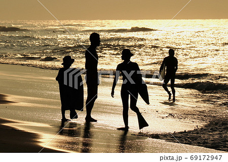夜明けの海辺のサーファー親子 69172947