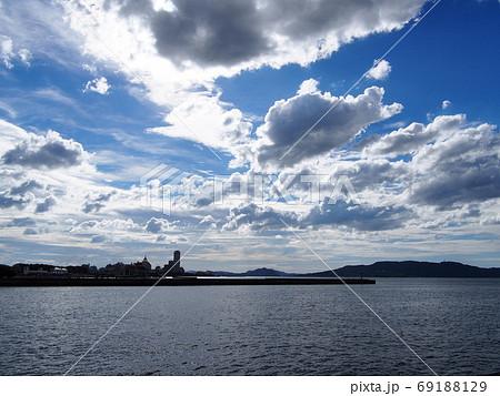 青空の下に広がる海と建物と遠くに見える島 69188129