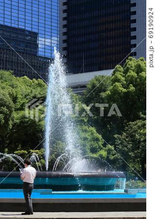 日比谷公園の噴水のそばにたたずむビジネスマン 69190924