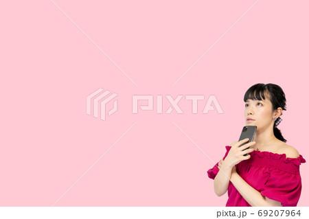 スマホを持って考える女性(ピンク背景) 69207964