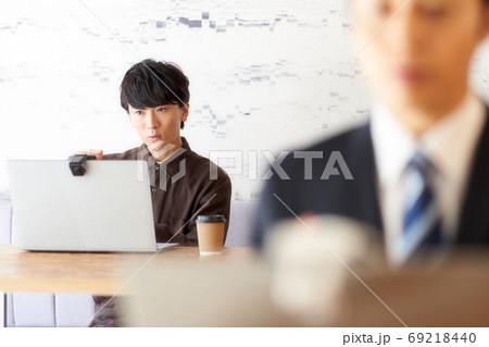 カフェでPCを使っている男性 ビジネスカジュアル 69218440