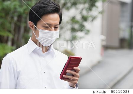 マスクをしてスマホを見る30代の日本人ビジネスマン 69219083