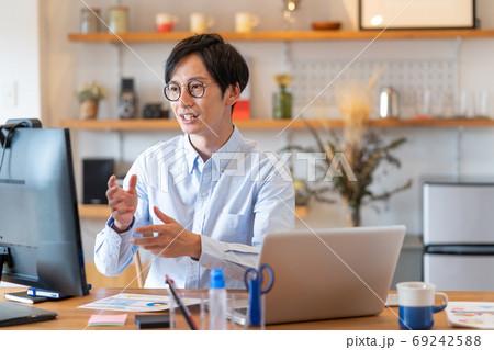テレワーク 自宅のリビングでweb会議をする笑顔の若い男性 69242588