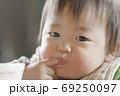 指を咥える赤ちゃん 69250097