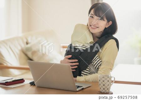 家で赤ちゃんの世話をしながテレワーク・リモートワーク・在宅ワークをする日本人女性イメージ 69257508