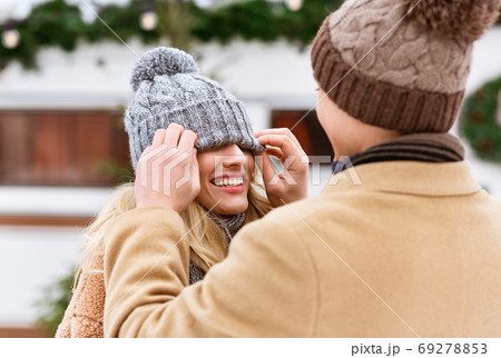 Romantic couple having fun outdoors in winter, man playing with girlfriend's hat 69278853