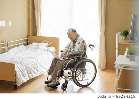 パソコンを見るシニア男性 介護施設 69284219