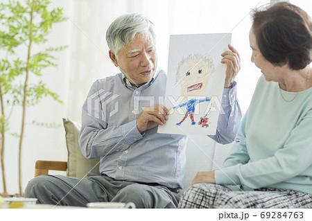 似顔絵を持って笑顔のシニア夫婦 69284763