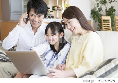 パソコンを見ながら電話をする家族 69289579