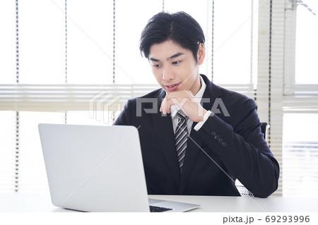 オフィスで笑顔でノートパソコンを操作する日本人男性ビジネスマン 69293996