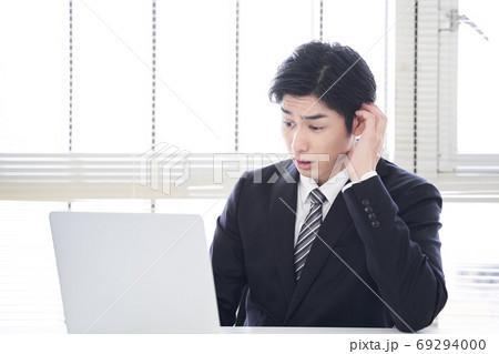 オフィスで困った表情でノートパソコンを操作する日本人男性ビジネスマン 69294000