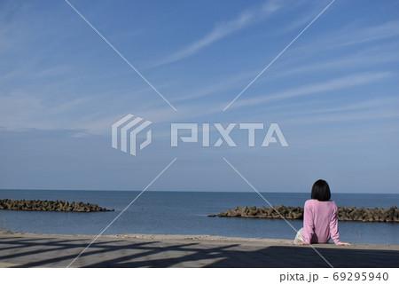 爽やかな海風を浴びながらくつろぐ女性 69295940