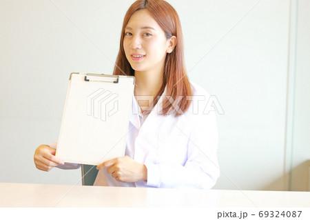 クリップボードを笑顔で見せる看護師 69324087