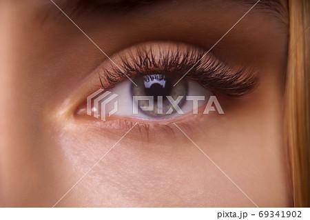 Eyelash Extension Procedure. Woman Eye with Long Eyelashes. Close up, selective focus. 69341902