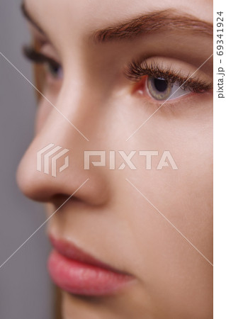 Eyelash Extension Procedure. Woman Eye with Long Eyelashes. Close up, selective focus. 69341924