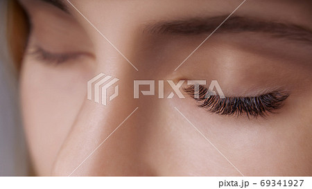 Eyelash Extension Procedure. Woman Eye with Long Eyelashes. Close up, selective focus. 69341927