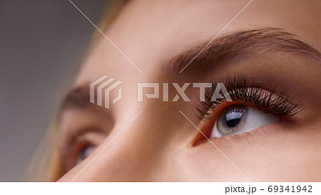 Eyelash Extension Procedure. Woman Eye with Long Eyelashes. Close up, selective focus. 69341942