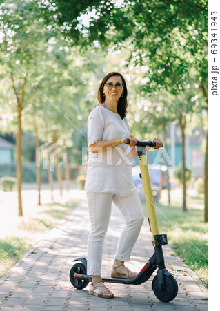 Joyful adorable senior woman using a scooter while riding in the park. Modern woman, a new generation. Healthy cheerful senior retired lady. Concept of Age Inclusivity and ecological transport 69341943