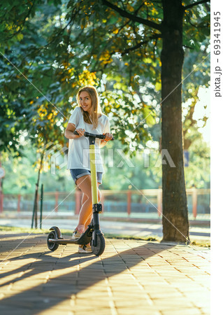 Smiling woman rides electric scooter or e-scooter in city park at sunset. Female using electric transport in urban park 69341945