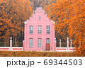 Old Dutch pink brick house with vintage fence in autumn 69344503