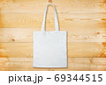Blank white fabric bag on wooden background. Plain white tote bag on natural wooden texture 69344515