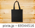 Black fabric bag on wooden background. Reusable black tote bag on wooden texture 69344516