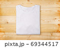 Blank white folded t-shirt on wooden background. Plain white tshirt on natural wooden texture 69344517