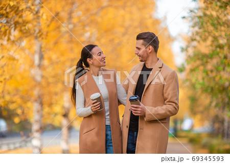 Happy family walking in autumn park on sunny fall day 69345593