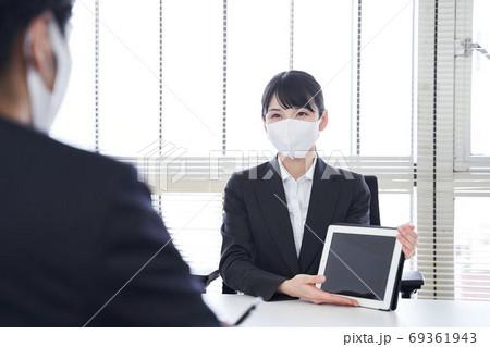 マスクを付けてオフィスで営業をする日本女性ビジネスウーマン 69361943