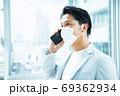 スマホで電話する男性会社員 69362934
