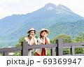 女子旅で由布岳を背景に記念撮影をする若い女性と友達 【9月】 69369947