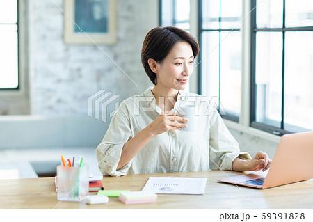 コーヒーを飲みながらテレワークする若い女性 69391828