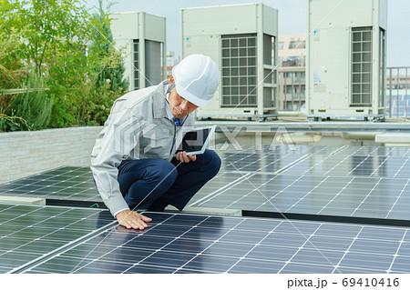 ソーラーパネルを点検する男性作業員 69410416