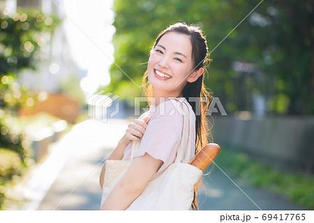 街中でエコバックを持つ笑顔の若い女性 69417765