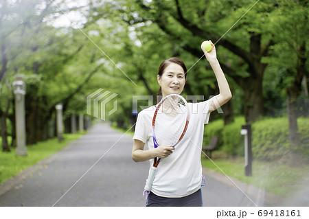 テニスラケットを持って立っているシニア女性 69418161