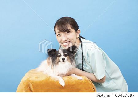 パピヨンと微笑む女性獣医師 69427697