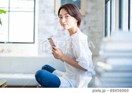 リビングでスマホを操作するミドルの女性 69456060