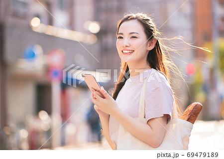 街中でスマホを持つ買い物帰りの若い女性 69479189