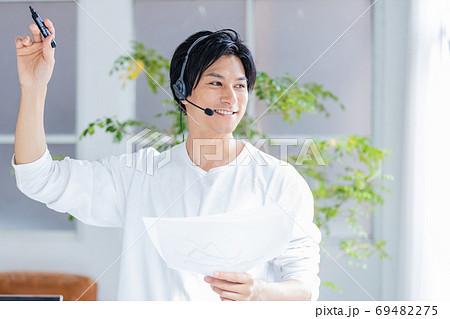ヘッドセットをつけて画面の外に向かって話をする若い男性 69482275