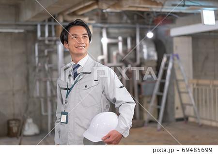 ヘルメットを片手に現場を確認する笑顔の監督 69485699