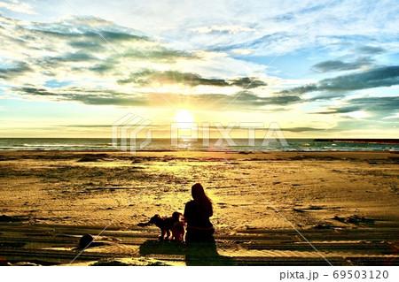 夕日を見ながら犬の散歩をする女性 69503120