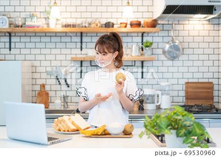 マウスガードをしてネット配信をしながら炭水化物ダイエットについてセミナーをしている若い料理研究家 69530960