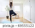 部屋の中で運動をする若い女性 69555122