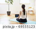 部屋の中で運動をする若い女性 69555123