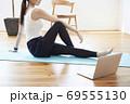 部屋の中で運動をする若い女性 69555130