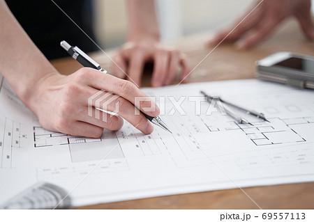 カジュアルなオフィスで打ち合わせをする日本人設計士 69557113